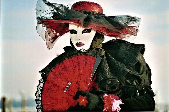 Woman with white mask, eyes outlined black, red hat and fan