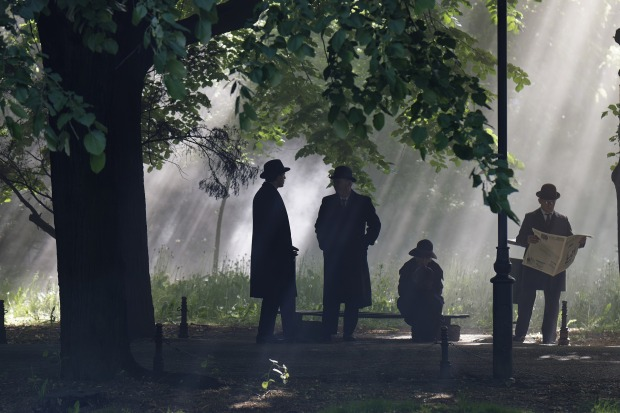 Three men and one woman under a tree, wearing hats, slanting sunbeams